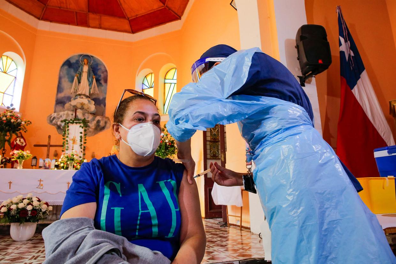 Een Chileense vrouw wordt gevaccineerd in een kerk. Beeld AFP
