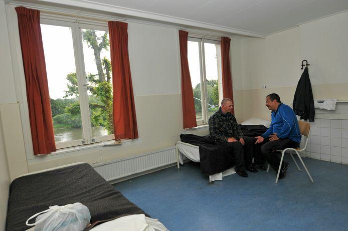 Een dakloze en een medewerker in een kamer in de daklozenopvang aan de Rijnkade.