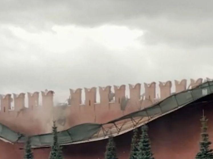 Stevige rukwind blaast stellingen over de muur van het Kremlin
