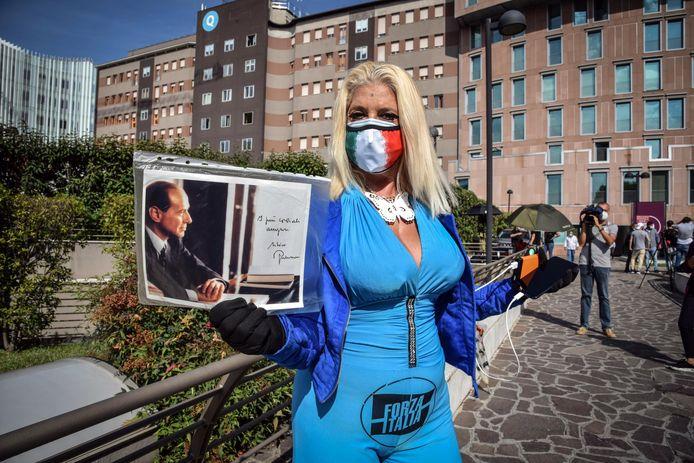 Een fan van Berlusconi voor het ziekenhuis waar hij wordt behandeld.
