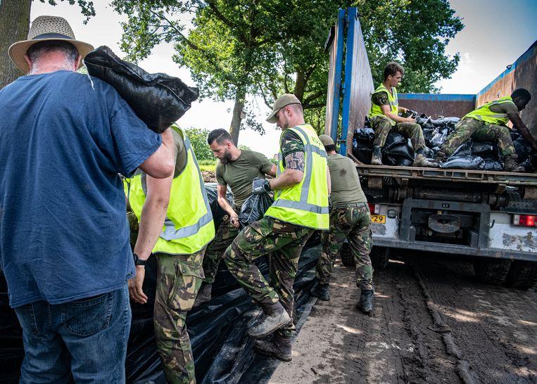 Militairen plaatsen extra dijkverzwaring  bij het dorp Well. Beeld Koen Verheijden