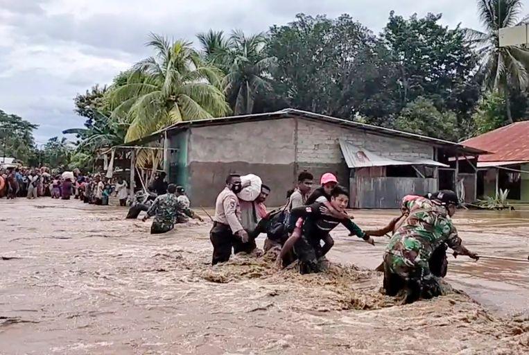 Inwoners van de Indonesische provincie Oost-Nusa Tenggara worden door soldaten uit de modderstromen gehaald. Beeld AP