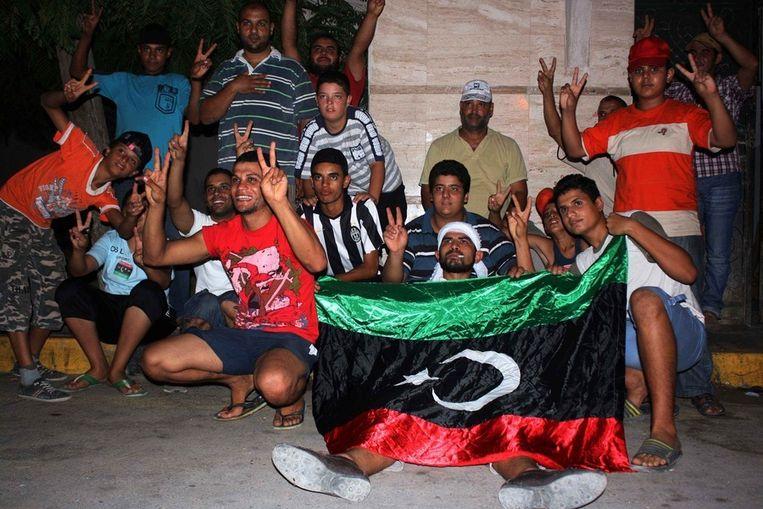 Rebellen in een buitenwijk van Tripoli poseren voor fotografen. Beeld afp