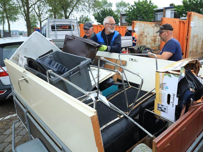 Vrijwilligers Wim de Feijter (links) en Stanny Gijsel (tweede van links) halen spullen bij mensen thuis op.