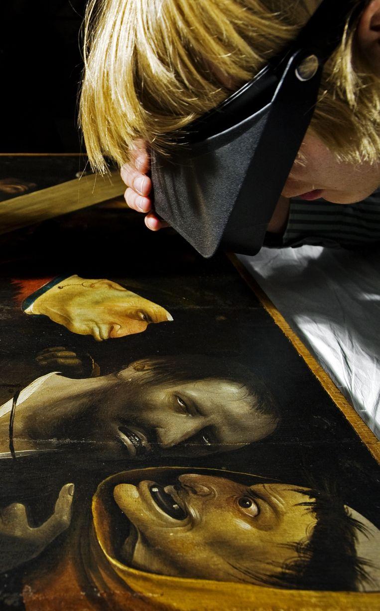 Een expert neemt het meesterwerk onder de loep. Beeld BELGAIMAGE