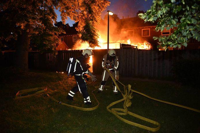 Brandweermannen proberen het vuur aan de Parallelweg in Almelo te bestrijden.