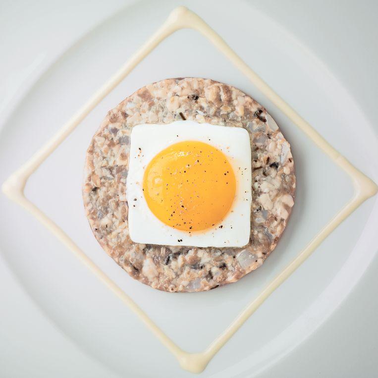 Steak  tartare met oester.  Op de allereerste  kaart die John en Esther Halvemaan in 1989 in hun nieuwe restaurant in Buitenveldert voerden, stond deze nieuwe versie van de klassieke steak tartaar: gehakte rundermuis, klassiek aangemaakt met ketchup, eidooier, cornichon en tabasco en geserveerd met een  gebakken eitje. Nieuw was de oester, die door het vlees werd gehakt. Ook de opmaak, met de saus van mayonaise en oestervocht in een strak vierkant, is typisch Halvemaan. Beeld Paul Ruigrok