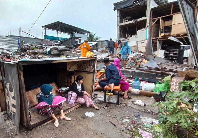 Gezinnen bij hun vernielde huizen.