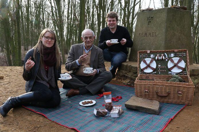Sara Barthier (diensthoofd Toerisme), toerismeschepen Etienne Decloet en chocolatier Olivier Verledens genieten op de Kemmelberg van een Heuvellandse bergsteen (zie inzet).
