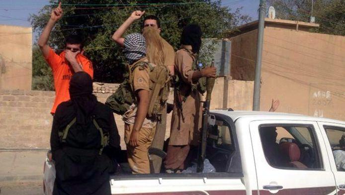 Gewapende Irakezen rijden door de straten van Tikrit