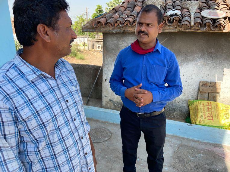 Vakbondsleider Swadesh Parkipandla (rechts) in gesprek met een teruggekeerde arbeidsmigrant. Beeld Aletta André
