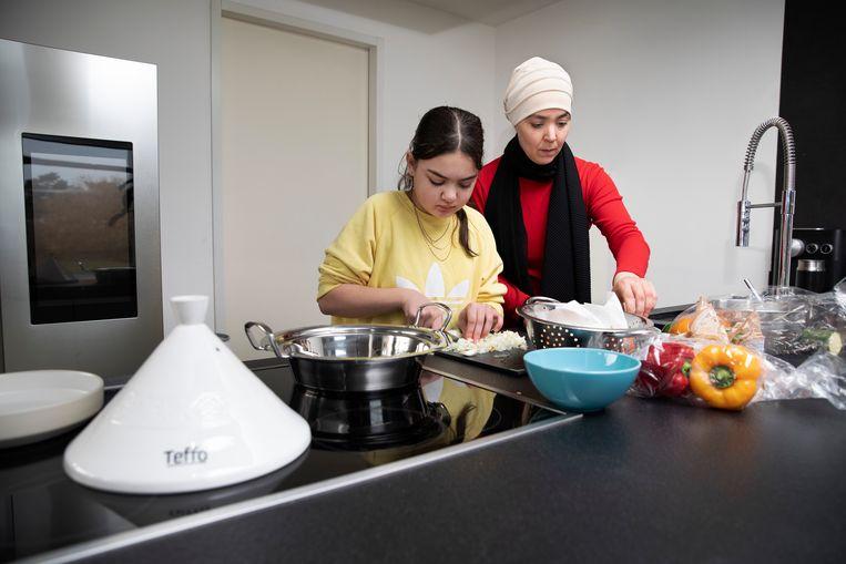 Esmah Lahlah bereidt met haar dochter Noor (11) het Marokkaanse gerecht tajine, dat zij door haar beperkte budget heeft herontdekt. Beeld Ton Toemen