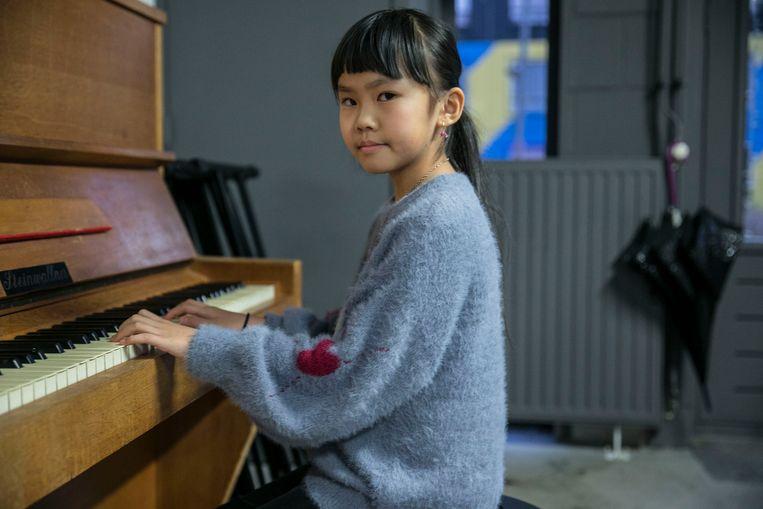 Gigi, negen jaar, oefent twee uur per dag op de piano. Beeld Amaury Miller