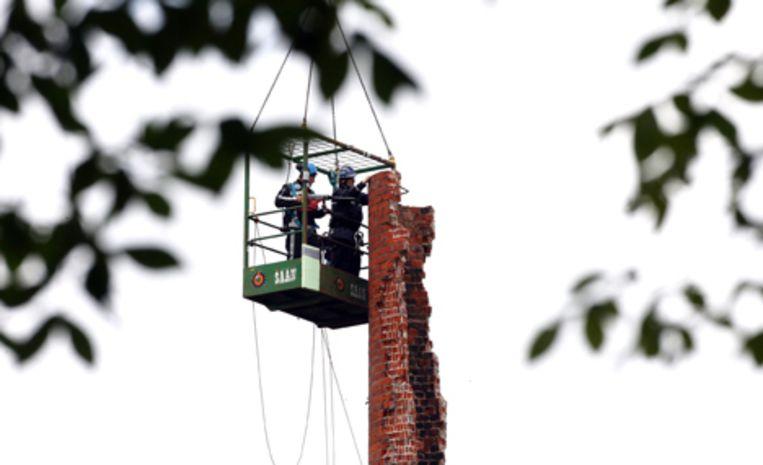 Slopers zijn zaterdag rond het middaguur begonnen de schoorsteen aan de Amsterdamse Da Costakade af te breken. Foto's ANP/Evert Elzinga Beeld