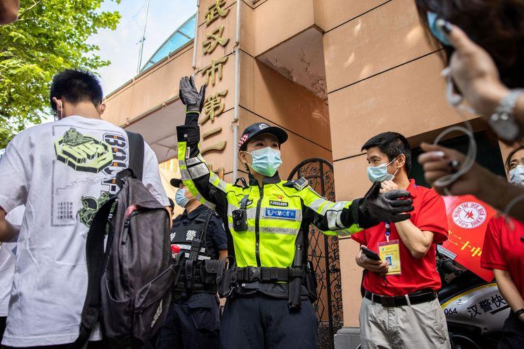 Een agent regelt de toegang tot de hal waar Chinese studenten het centrale examen 'gaokao' gaan afleggen.  Beeld AFP