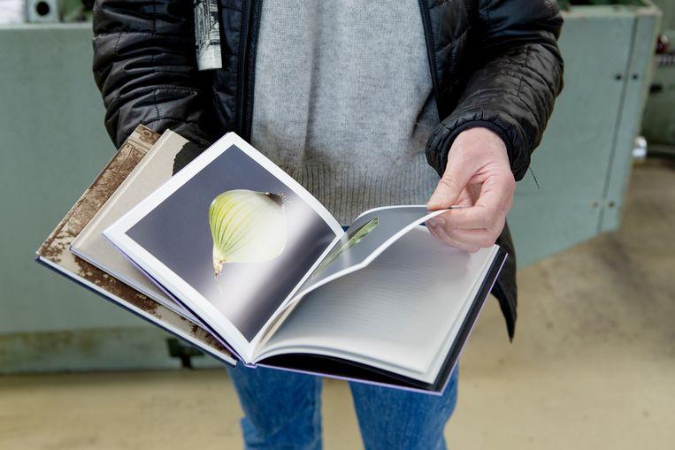 Grafisch ontwerper Tessa van der Waals toont ingestoken pagina's op een andere papiersoort. Beeld Pauline Niks