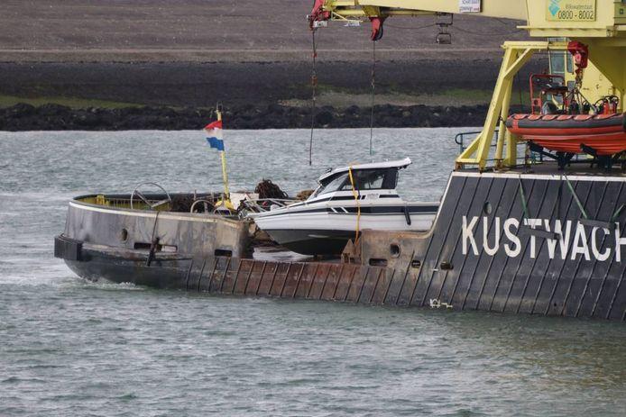 De Kustwacht heeft het omgeslagen bootje geborgen en brengt het de haven van Neeltje Jans binnen.