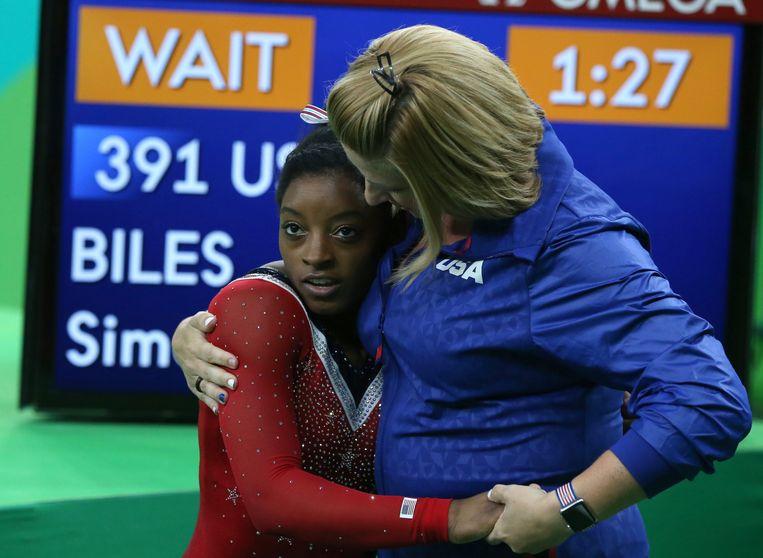 Simon Biles (l) uit de VS wordt omarmd door haar coach Aimee Boorman na deelname aan de finale van de Olympische Spelen van Rio 2016. Beeld EPA
