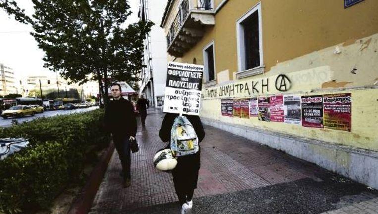 Een actievoerder draagt een bord met de tekst 'belast de rijken', onderweg naar een demonstratie in Athene tegen de bezuinigingen. (FOTO EPA) Beeld