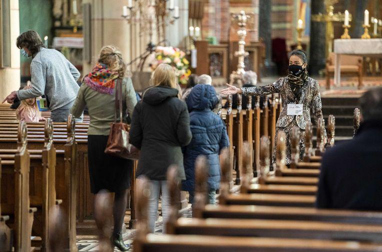 Bezoekers krijgen een plaats toegewezen tijdens de viering in de Vituskerk in Hilversum. Beeld ANP
