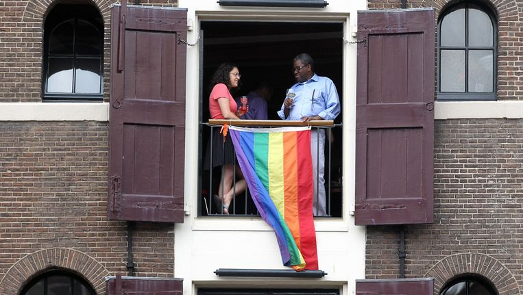 Archieffoto. Toeschouwers wachten in een appartement langs de Prinsengracht op de start van de botenparade van de Gay Pride Beeld anp