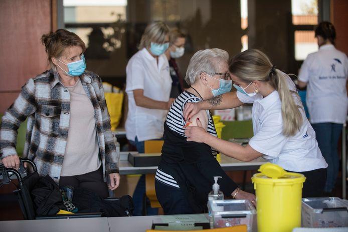 De 84 jarige Mia van Haaren uit Tiel krijgt de griepprik onder toeziend oog van haar dochter Suzanne van Haaren (links, 52 jaar).