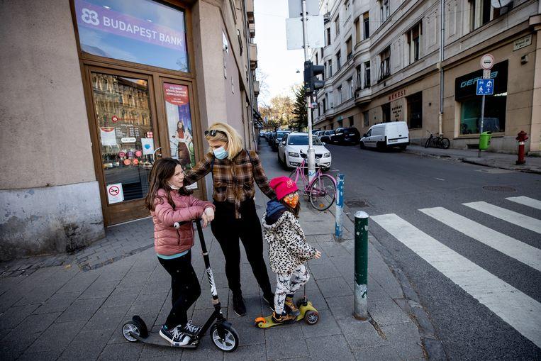 Een moeder met twee kinderen op straat in Boedapest. Wie belooft drie kinderen op de wereld te zetten, kan een goedkope lening van 30.000 euro afsluiten. Na de geboorte van het derde kind wordt de lening omgezet in een gift. Beeld Getty Images