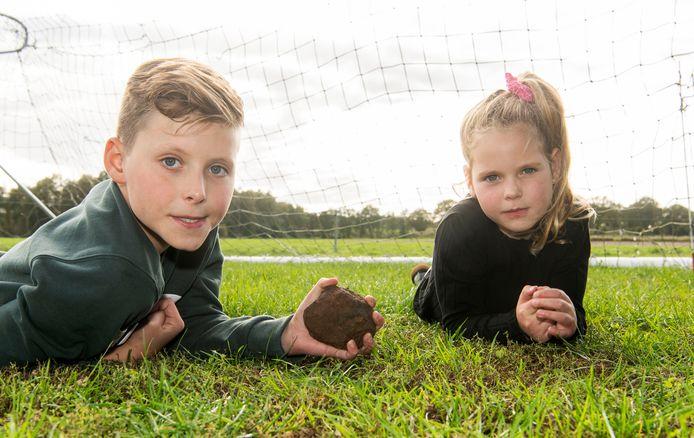 Jans Klein Gebbink met de bijzondere steen die vlak bij hem neerkwam op het grasveldje bij de boerderij. Naast hem zijn zus Jula.