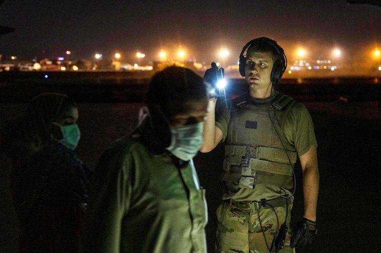 Een Amerikaanse militair schijnt evacués bij die een militair toestel betreden.  Beeld via REUTERS
