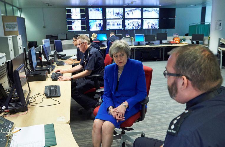 Premier Theresa May in gesprek met een werknemer van het Britse Border Force Command Centre op luchthaven Heathrow in Londen. Beeld Reuters