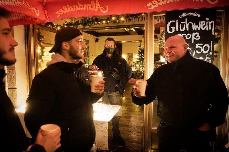 Matthias Kutschmar (m.) achter zijn standje in de Stargarder Strasse: 'Een kleine goedmaker voor dit jaar waarin je als ondernemer om elke euro moet strijden. Maar een lockdown is verstandiger' Beeld DANIEL ROSENTHAL