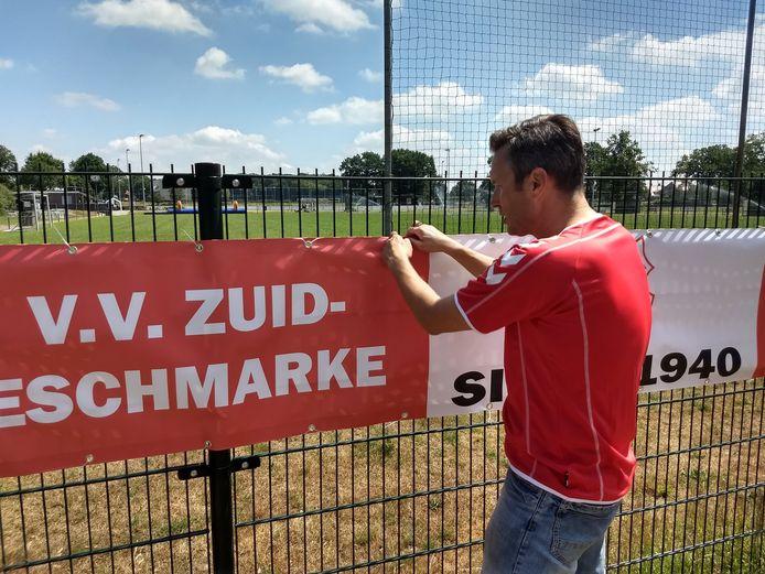 Voorzitter Bas Veenendaal bevestigt het spandoek van Zuid Eschmarke aan het hek van Sportclub Enschede.