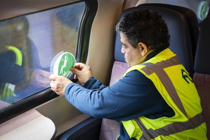 Een monteur van de NS plakt stickers in een trein, die aangeven op welke stoelen wel of niet mag worden gezeten.