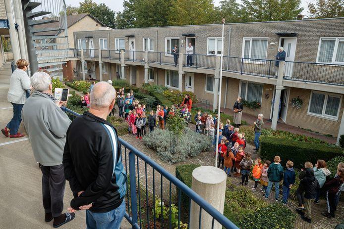 Kinderen van basisschool De Klankhof zingen liedjes voor de oudere bewoners in de buurt. De binnentuin van flat de Panfluit bood een goede akoestiek voor de Oudhollandse liedjes.