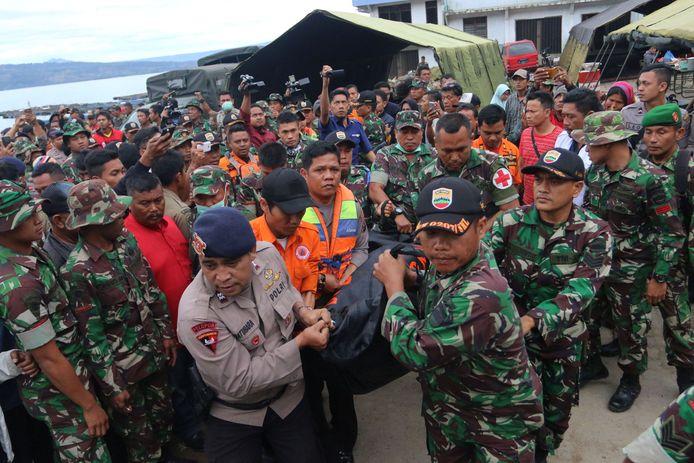 Indonesische veiligheidsdiensten en hulpverleners bergen het lichaam van een slachtoffer van het veerbootdrama.