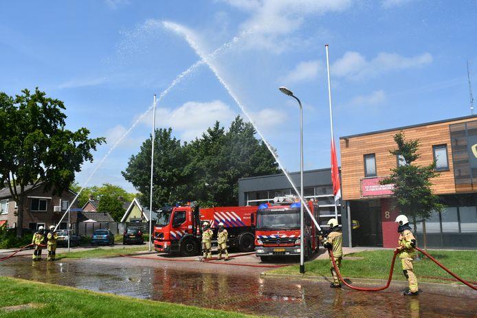 Brandweerlieden creëren bij de kazerne in Vroomshoop een erehaag van water voor overleden collega's.