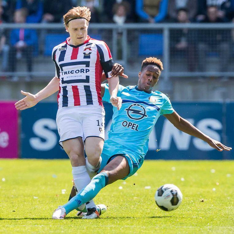 Terence Kongolo zet een tackle in op Guus Hupperts van Willem II. Beeld anp