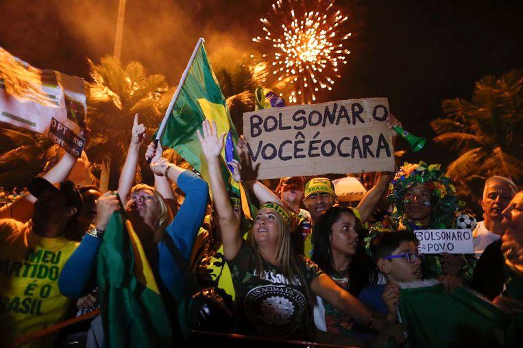Aanhangers van de nieuwe president Jair Bolsonaro vieren feest voor zijn huis in een chique wijk van Rio de Janeiro. Beeld AFP