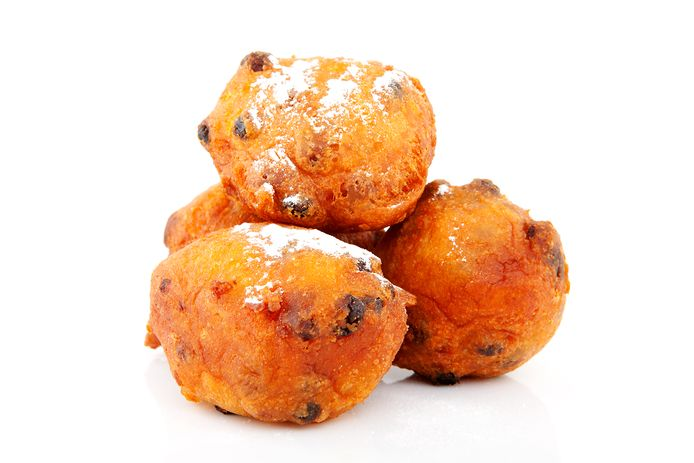 Pile of Dutch donut also known as oliebollen, traditional New Year's eve food isolated on white background