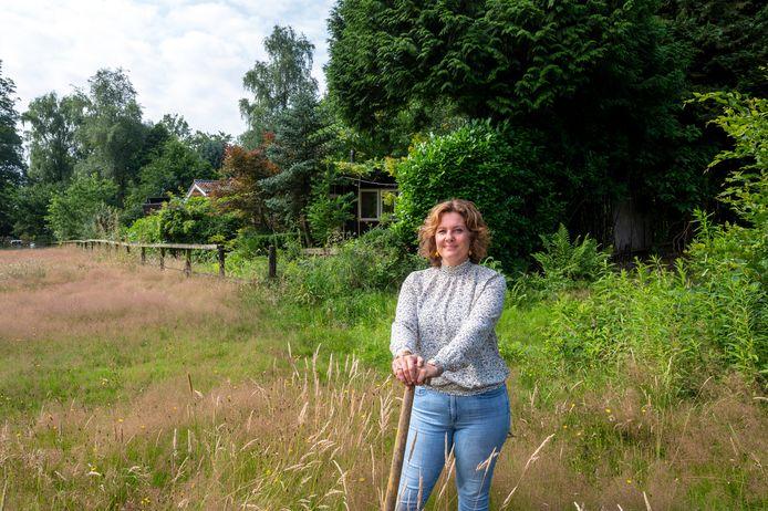 Arlette Groenewoud met achter zich haar in het groen verborgen camping Buitenverblijf Het Groene Woud. De camping moet op de schop.