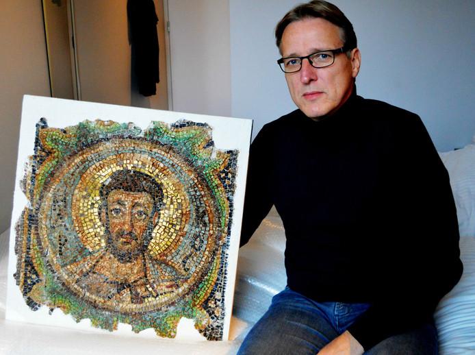 De Nederlandse kunstdetective Arthur Brand poseert op een hotelkamer in Den Haag met het gestolen mozaïek.