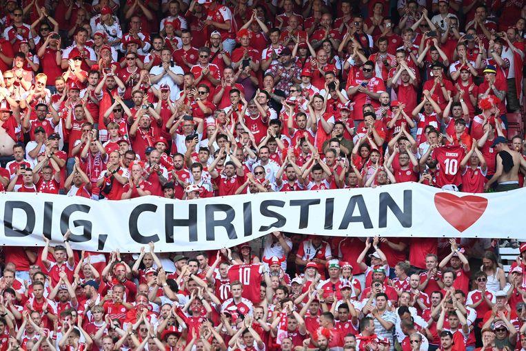 Deense supporters applaudisseren tijdens de wedstrijd Denemarken-België voor Christian Eriksen,  de nummer tien van Denemarken die enkele dagen eerder vocht voor zijn leven als gevolg van een hartstilstand.  Beeld AFP