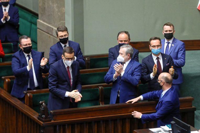 Poolse kabinetsleden, onder wie premier Mateusz Morawiecki (linksvoor), vierden in mei dit jaar dat het Poolse parlement het coronaherstelfonds van de Europese Unie had goedgekeurd. Nu staat de Poolse aanvraag voor dat geld op de tocht. Beeld EPA