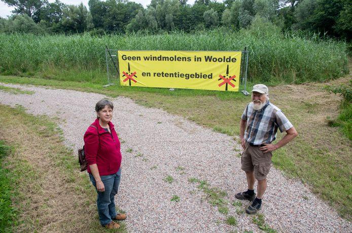 De strijd tegen de mogelijke komst van windmolens in Woolde gaat door. Hier twee initiatiefnemers van het eerste uur, Mariska van Doorn en Piet Vendel, bij een spandoek in het retentiegebied.