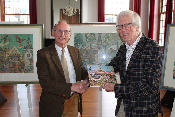 Liers burgemeester Frank Boogaerts krijgt een exemplaar van 'Als ik teken ben ik op reis', een naslagwerk over tekenaar Jaap Oudes. De man rechts op de foto is Jan Oud, één van de auteurs.