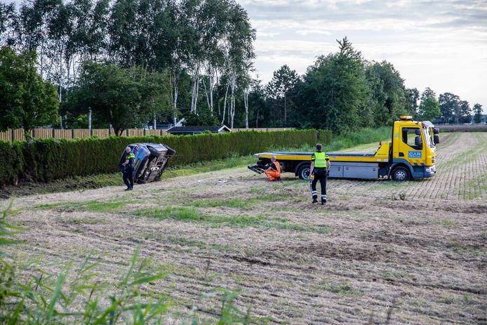 Auto ondersteboven in weiland in Kruisland