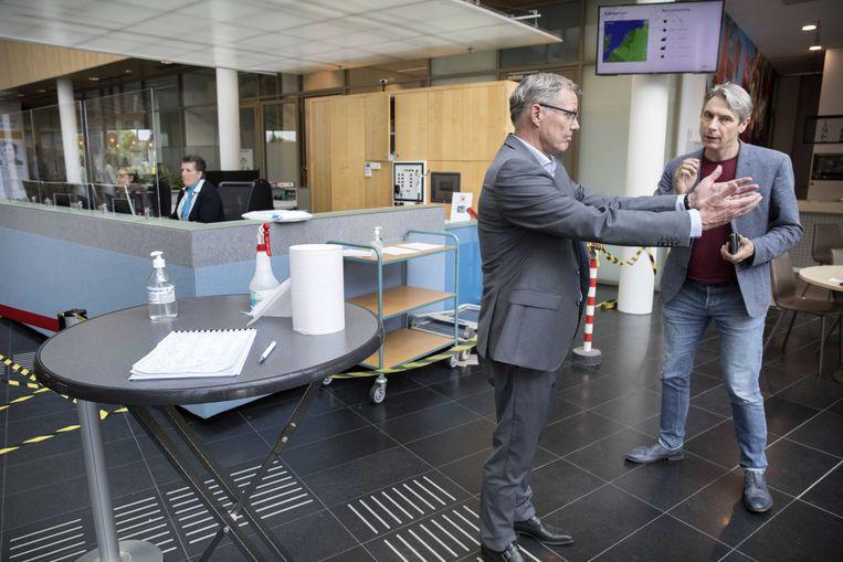 FNV-voorzitter Han Busker en vice-voorzitter Tuur Elzinga staan in het hoofdkantoor de pers te woord. Beeld ANP