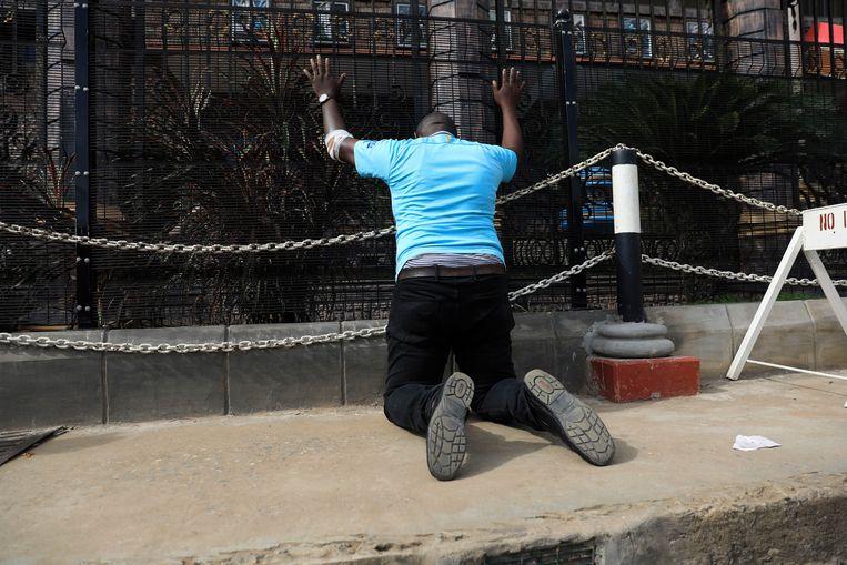 Een van de volgelingen van TB Joshua bidt na diens overlijden voor zijn kerk in Lagos. Beeld AP