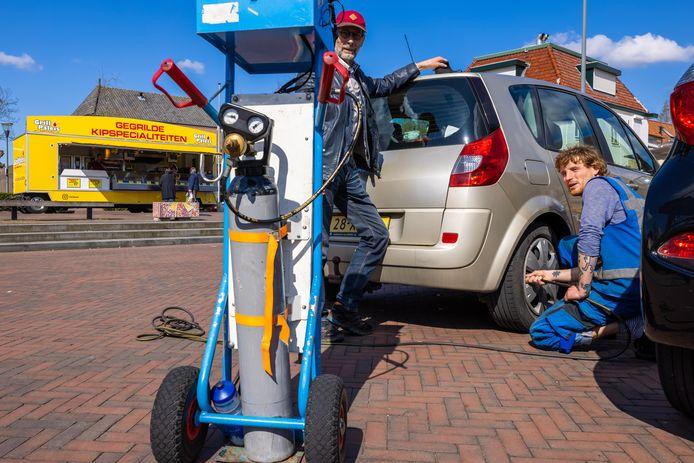 Op het Dorpsplein in Waspik konden mensen zaterdag de bandenspanning van hun auto laten meten. Een goede bandenspanning zorgt voor zuiniger en veiliger rijden. Roland Broos meet de banden van de auto van Kees.