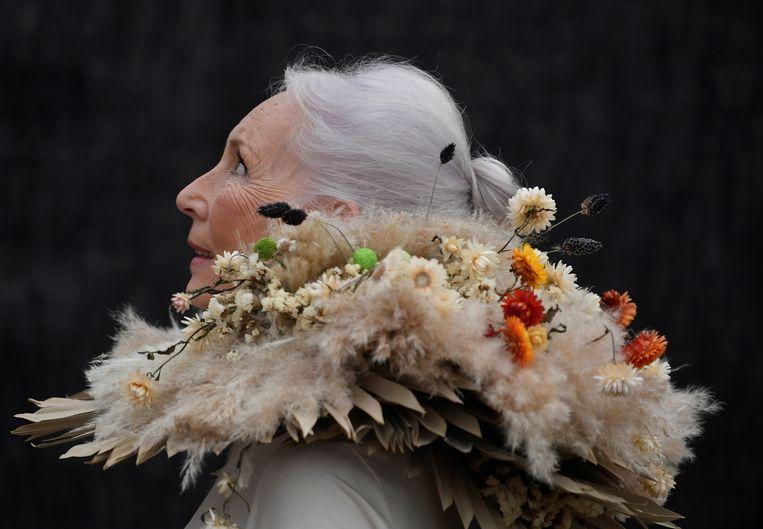 Een bezoeker van de Chelsea Flower Show in London draagt een kraag van droogbloemen. Beeld REUTERS